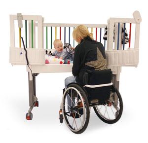 Elmanövrerad höj- och sänkbar spjälsäng för förälder i rullstol